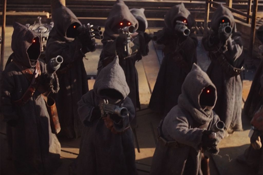 The off-world Jawas take aim at the Mandalorian as he climbs to the top of their sand crawler